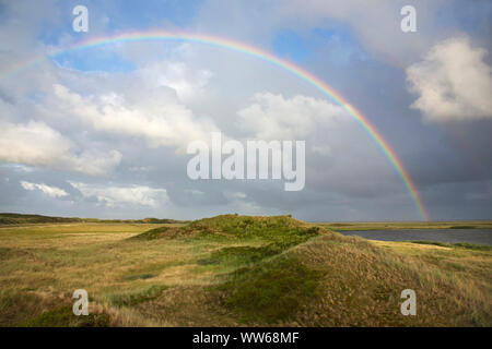 Rainbows above the green dunes at the Schloppsee on the island Langeoog. - Stock Photo