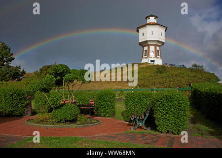 View from a small park on a rainbow behind the old water tower, the landmark of the island Langeoog. - Stock Photo