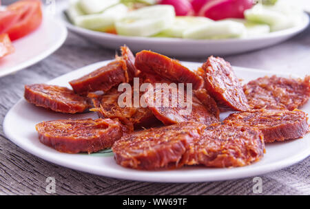 Spicy red Iberian Sausage 'Chorizo Iberico' on a plate served as typical Spanish Tapa in Spain. Empty copy space for Editor's text. - Stock Photo