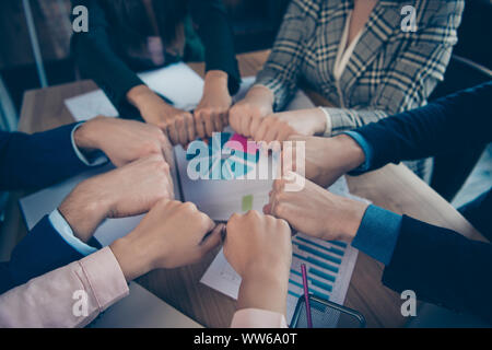 Cropped close-up view of stylish sharks agent broker putting fists in round circle over desktop desk table charts diagram graph graphic data paper - Stock Photo