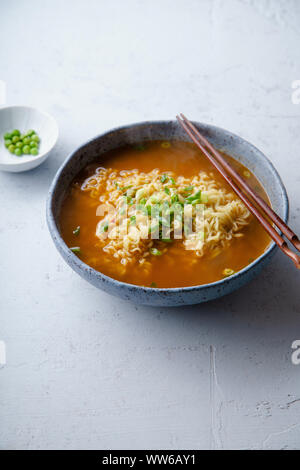 Easy japanese ramen with noodles, pork broth, egg and leek in handmade blue ceramic bowl with wooden chopsticks. Concrete background - Stock Photo