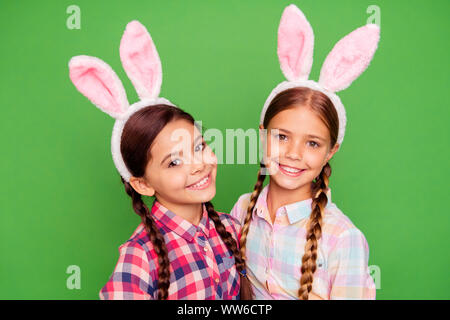 Close-up photo portrait of couple of positive cheerful glad with teeth smile pre teen scholl girls holding painted chocolate eggs looking at camera - Stock Photo