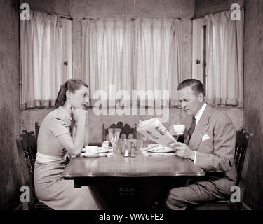 1930s 1940s ANGRY IGNORED WOMAN WIFE AT BREAKFAST DINNER TABLE WITH INSENSITIVE HUSBAND DRINKING COFFEE AND READING NEWSPAPER - d1835 HAR001 HARS FEMALES MARRIED SPOUSE HUSBANDS HOME LIFE COPY SPACE FRIENDSHIP HALF-LENGTH LADIES PERSONS CARING MALES B&W PARTNER SADNESS SUIT AND TIE DREAMS DISTRESSED IGNORING AND PRIDE HURT CONNECTION IGNORED DISPLEASURE PERSONAL ATTACHMENT AFFECTION ANNOYANCE BAY WINDOW EMOTION EMOTIONAL INSENSITIVE IRRITATED MID-ADULT MID-ADULT MAN MID-ADULT WOMAN TOGETHERNESS UNAWARE WIVES BLACK AND WHITE CAUCASIAN ETHNICITY DISPLEASED HAR001 INDIFFERENT OBLIVIOUS - Stock Photo