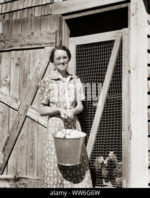 1930s SMILING WOMAN WEARING EYEGLASSES LOOKING AT CAMERA HOLDING PAIL OF FRESHLY LAID EGGS STANDING AT DOOR TO CHICKEN COOP - p2820 HAR001 HARS LADIES PERSONS UNITED STATES OF AMERICA FARMING CONFIDENCE EYEGLASSES AGRICULTURE B&W NORTH AMERICA EYE CONTACT BRUNETTE NORTH AMERICAN HAPPINESS CHEERFUL PAIL EXTERIOR FARMERS COOP PRIDE OCCUPATIONS SMILES CONNECTION CHICKENS JOYFUL FRESHLY MID-ADULT MID-ADULT WOMAN POULTRY BLACK AND WHITE CAUCASIAN ETHNICITY HAR001 LAID OLD FASHIONED - Stock Photo