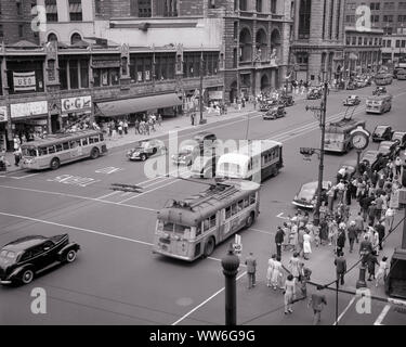 1940s BROAD STREET & MARKET INTERSECTION BUSES CARS PEDESTRIANS DOWNTOWN NEWARK NEW JERSEY USA - q42250 CPC001 HARS B&W NORTH AMERICA DOWNTOWN NORTH AMERICAN HIGH ANGLE INTERSECTION AUTOS PROGRESS BROAD NJ STORES TROLLEY NEWARK AUTOMOBILES TROLLEYS VEHICLES NEW JERSEY TRACKLESS TROLLEY BUSES COMMERCE ELECTRIC BUS STREET SCENE STREETCARS TROLLEY BUS BLACK AND WHITE BUSINESSES CITYSCAPE OLD FASHIONED PUBLIC TRANSPORTATION STREETCAR THOROUGHFARE TRAM TROLLEY CAR - Stock Photo