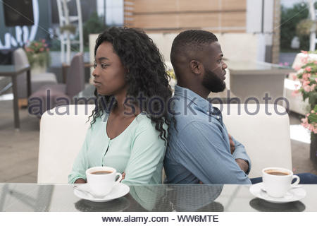 Unhappy angry african couple with serious problems in relations sitting back to back in cafe - Stock Photo