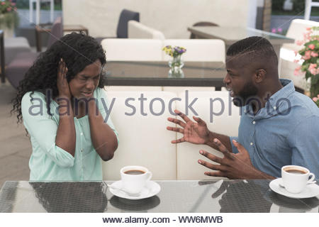 Young african couple arguing in a cafe. Relationship problems. - Stock Photo