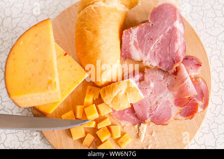Ham, cheese and bread on a wooden cutting board. The breakfast in the village. Snack with beer or wine. - Stock Photo