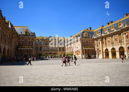 Paris / France - July 6, 2019: Groups of tourists in main square of Versailles Palace, summer time. - Stock Photo