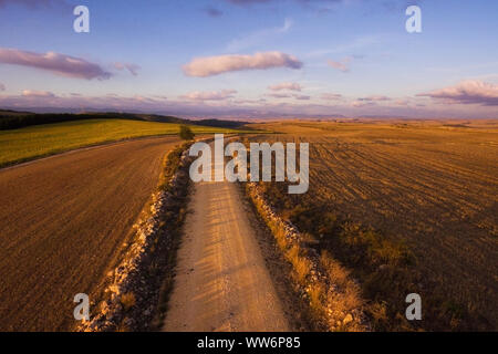 Aerial view of rural road in beautiful countryside landscape at sunset . - Stock Photo
