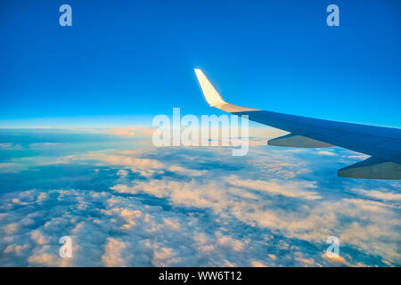 The wing of the aircraft is illuminated by the evening sunlight during the flight above the clouds in Europe - Stock Photo