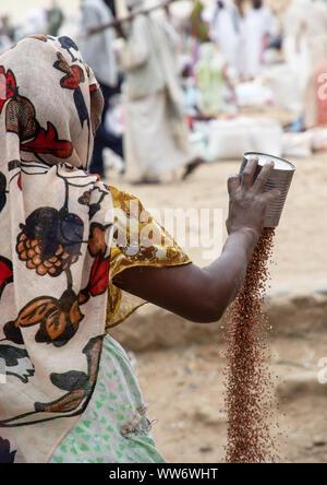 Eritrean woman sleving teff in the street, Semien-Keih-Bahri, Keren, Eritrea - Stock Photo