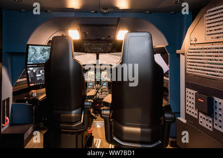 Cabin of a large airliner simulator. View of the cockpit and seats in the A320 airbus simulator. - Stock Photo