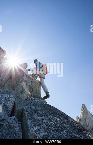 Climber climbing the summit of Dent de Tsalion via Arolla, Val d'Hérens, Valais, Switzerland - Stock Photo