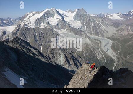 Climber climbing the summit of Dent de Tsalion, view of Pigne d'Arolla and Mont Blanc de Cheilon over Arolla, Val d'Hérens, Valais, Switzerland - Stock Photo