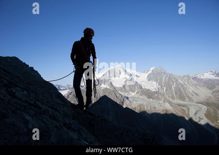 Climbing the summit of Dent de Tsalion over Arolla with views of Pigne d'Arolla and Mont Blanc de Cheilon, Val d'Hérens, Valais, Switzerland - Stock Photo