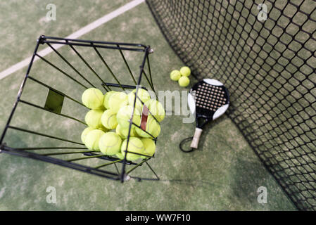 Paddle tennis objects on turf, balls, racket, net…focus on basket balls, - Stock Photo