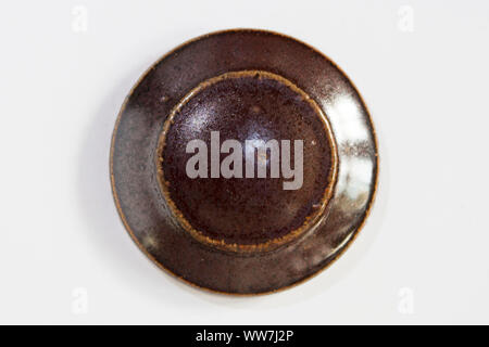 round clay probe with brown glossy glaze - Stock Photo