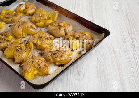Homemade garlic thyme smashed potatoes on a tray, side view. Copy space. - Stock Photo