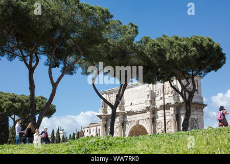 Italy, Rome, people walking along a way to the Coliseum, in the background Meta Sudans - Stock Photo