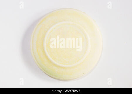 round clay sample covered with cream matte glaze - Stock Photo