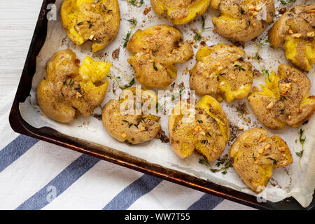 Homemade garlic thyme smashed potatoes, top view. Flat lay, overhead, from above. Close-up. - Stock Photo