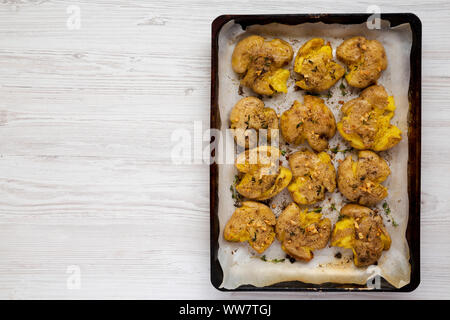 Homemade garlic thyme smashed potatoes on a tray, top view. Flat lay, overhead, from above. Copy space. - Stock Photo