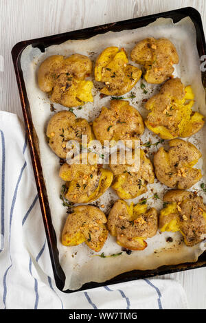 Homemade garlic thyme smashed potatoes on a tray, top view. Flat lay, overhead, from above. Closeup. - Stock Photo