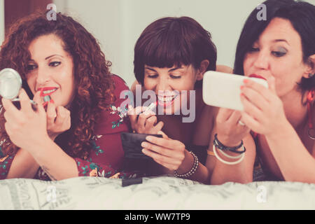 three females friends stay together lay down on the bed doing make up before go out to have party night. friendship concept one of them use a mobile phone like a mirror to check the quality of the work - Stock Photo