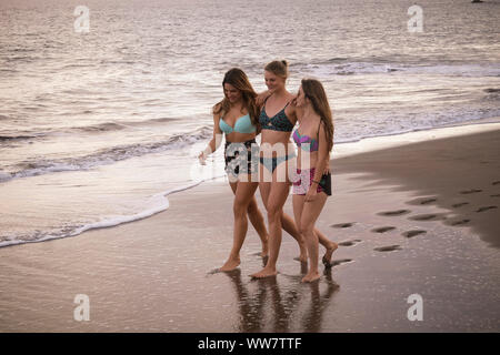 three caucasian cheerful young women walk together hugged on the shore at the beach. summer lifestyle outdoor activity for beautiful girls in vacation. smiling days and happiness - Stock Photo