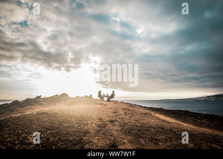 couple enjoying the outdoor freedom and leisure activity sitting in front of the ocean. travel and alternative vacation concept for happy lifestyle people together. great sky and clouds over a mountain - Stock Photo