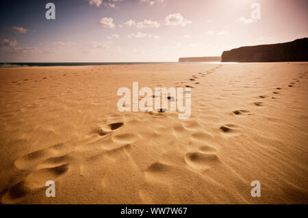infinite beach in portugal with yellow sand and footprint. mountains and rocks. travel and vacation concept with no tourists and tourism - Stock Photo