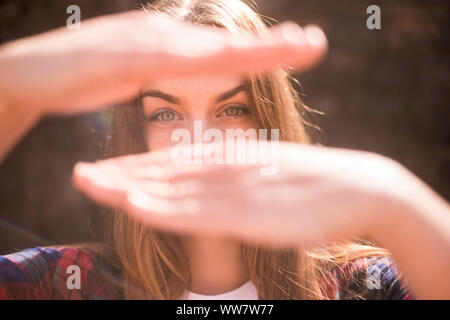 sunny portrait of beautiful model caucasian with blue eyes in backlight with hands in front of her face to hidden the mouth. bokeh defocused background - Stock Photo