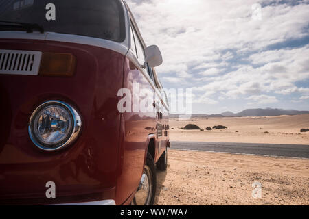 vintage style bus old parked near a road the cross the desert of corralejo in fuerteventura. travel concept for alternative vacation - Stock Photo