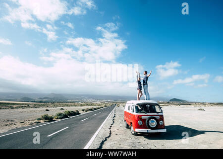 hippy style for an alternative vacation time outdoor leisure activity for young couple caucasian beautiful staying on the rooftop of a vintage van near a long road for travel concept. - Stock Photo