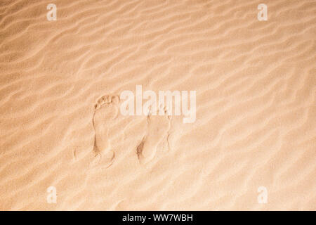 single pair of man or woman footsteps on the virgin sand at the beach in Fuerteventura. Summer concept. Nudism barefoot. - Stock Photo