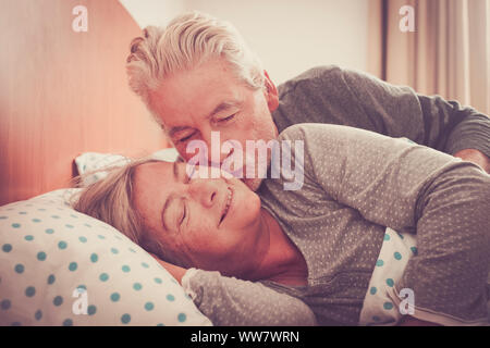 Couple of senior man and woman waking up and smiling with a hug while are in the bed at home. Vintage filter and light in the back. The man kiss the woman with love - Stock Photo