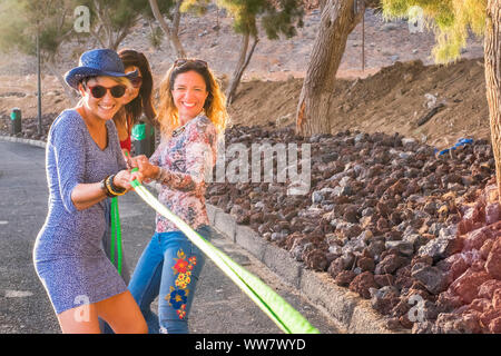 group of females friends with colored and happy clothes casual style enjoy together playing with a cord. happy outdoor leisure activity and smile. enjoy lifestyle and stay young - Stock Photo