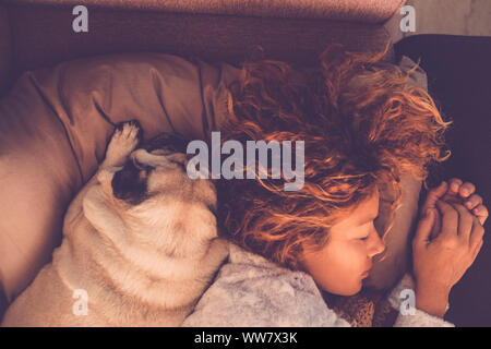 friendship concepts for 40s woman sleeping with her best firends pug dog at home. Both on the pillow and brown warm tones. Dreaming together. Love and friendship image mood - Stock Photo