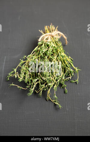 Raw organic fresh thyme on a black background, low angle view. - Stock Photo