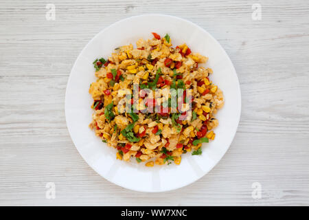 Homemade southwestern egg scramble on a white plate on a white wooden background, top view. Flat lay, overhead, from above. - Stock Photo