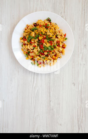 View from above, homemade southwestern egg scramble on a white plate on a white wooden background. Flat lay, top view, from above. Copy space. - Stock Photo