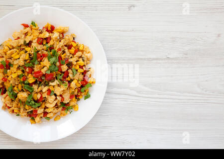 Homemade southwestern egg scramble on a white plate on a white wooden surface. Flat lay, top view, from above. Copy space. - Stock Photo