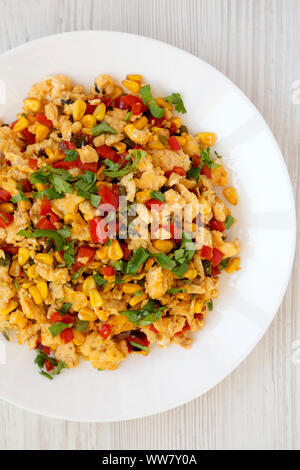 Overhead view, homemade southwestern egg scramble on a white plate on a white wooden background. Flat lay, top view, from above. Close-up. - Stock Photo