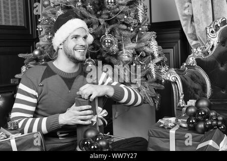Opening Christmas present. Guy is celebrating Christmas at home. Man in santa hat hold Christmas presents. Happy man with xmas gift boxes. Delivery Ch - Stock Photo