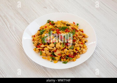 Homemade southwestern egg scramble on a white plate on a white wooden background, side view. - Stock Photo