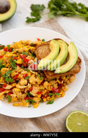 Homemade southwestern egg scramble with toast on a white plate on a white wooden background, side view. Close-up. - Stock Photo