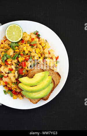 Overhead view, homemade southwestern egg scramble with toast on a white plate over black background, top view. Flat lay, from above. Copy space. - Stock Photo