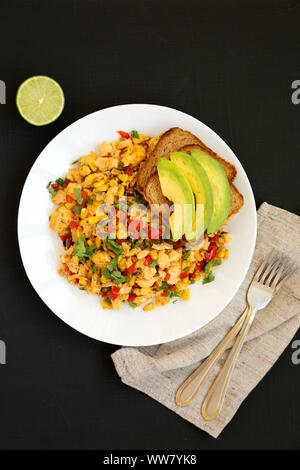 Homemade southwestern egg scramble with toast on a white plate on a black background, top view. Flat lay, overhead, from above. Close-up. - Stock Photo