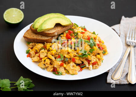 Homemade southwestern egg scramble with toast on a white plate on a black background, low angle view. Close-up. - Stock Photo